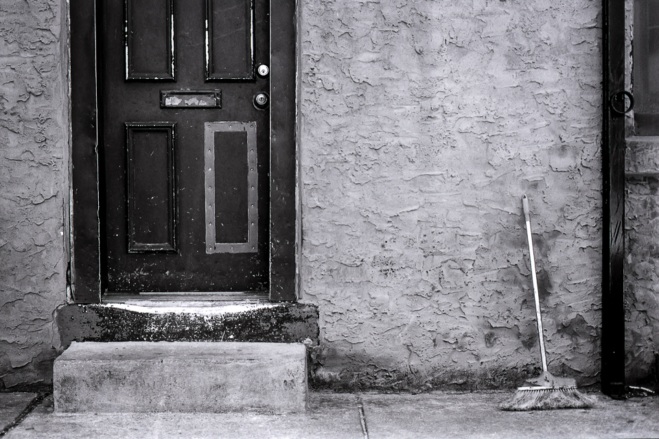 This composition is about vertical lines. The door is on the left third, the broom just outside the right third.