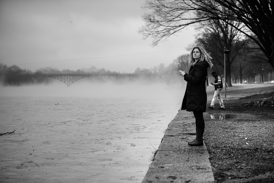 The fog on the river, despite being in the background, gives critical context as to why the woman (middleground) is standing on the wall (foreground)